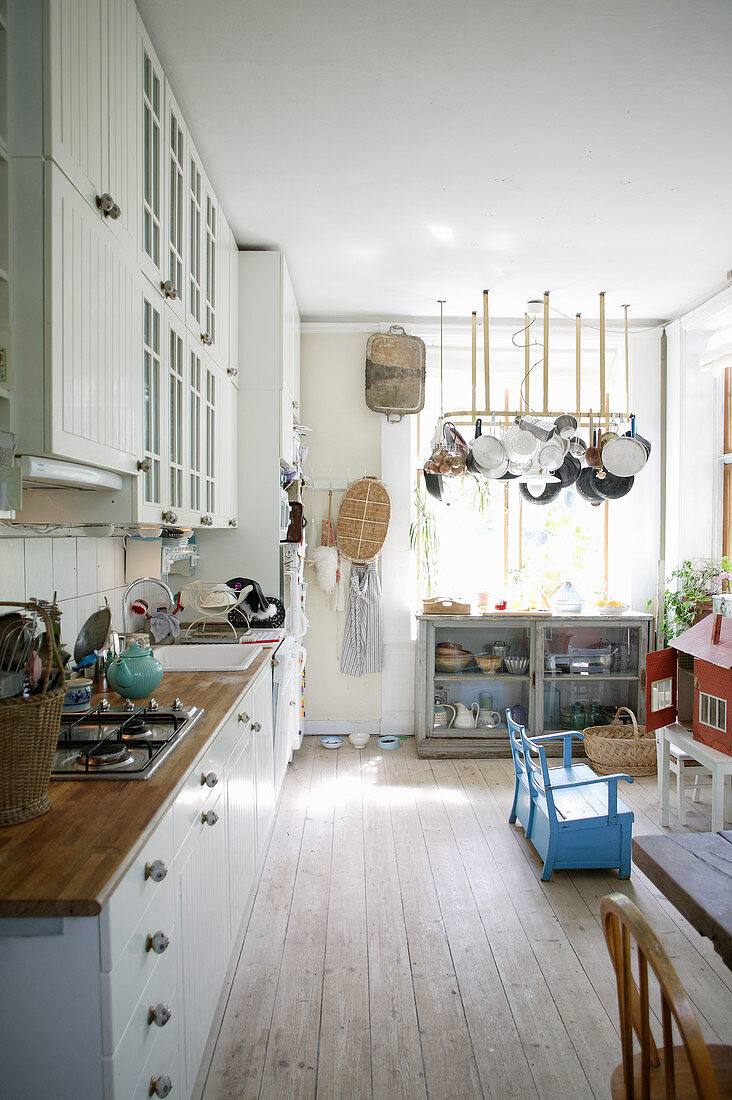 Kitchen-dining room in country-house style with board floor and children's play area