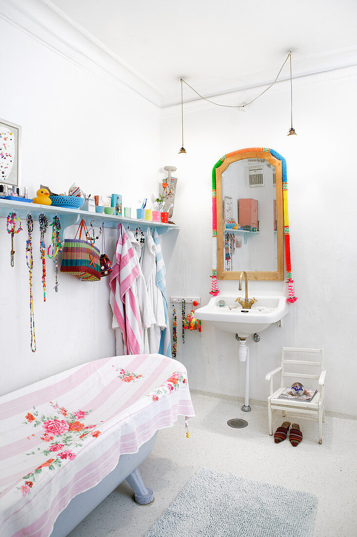 Free-standing bathtub in white bathroom with brightly coloured accents