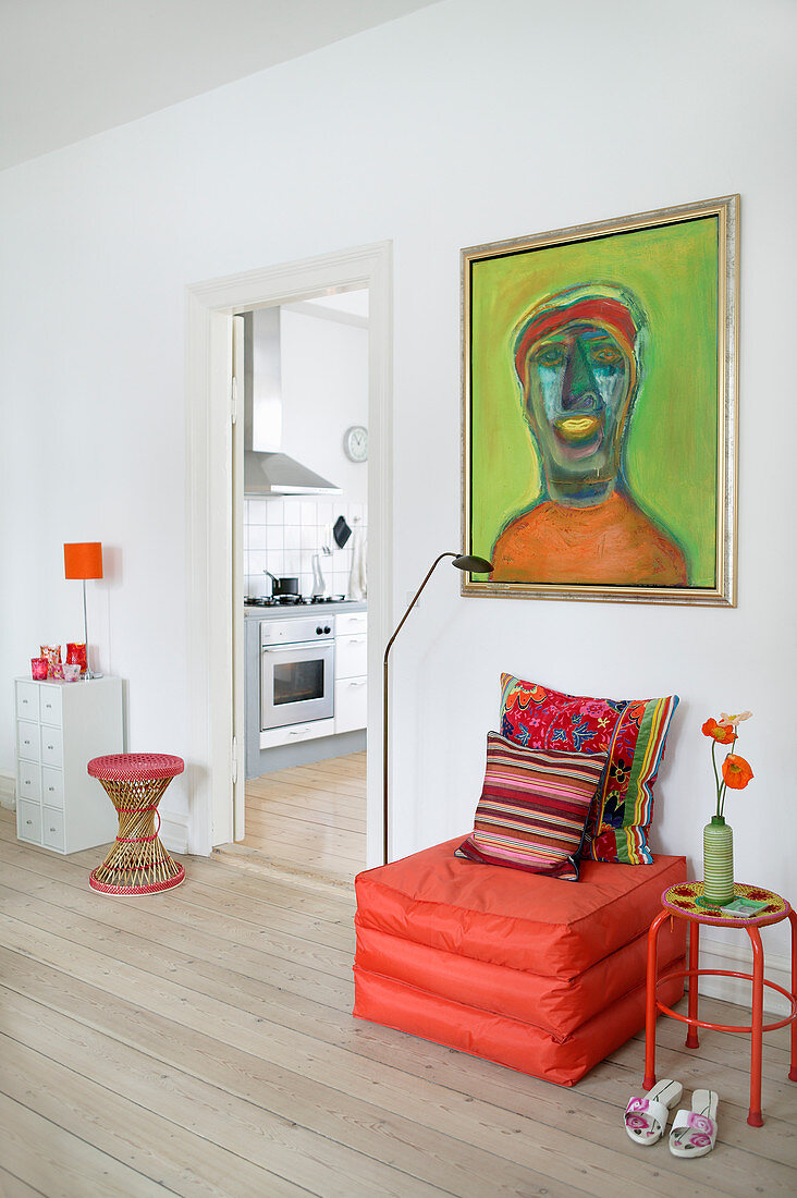Orange pouffe below green painting in living room