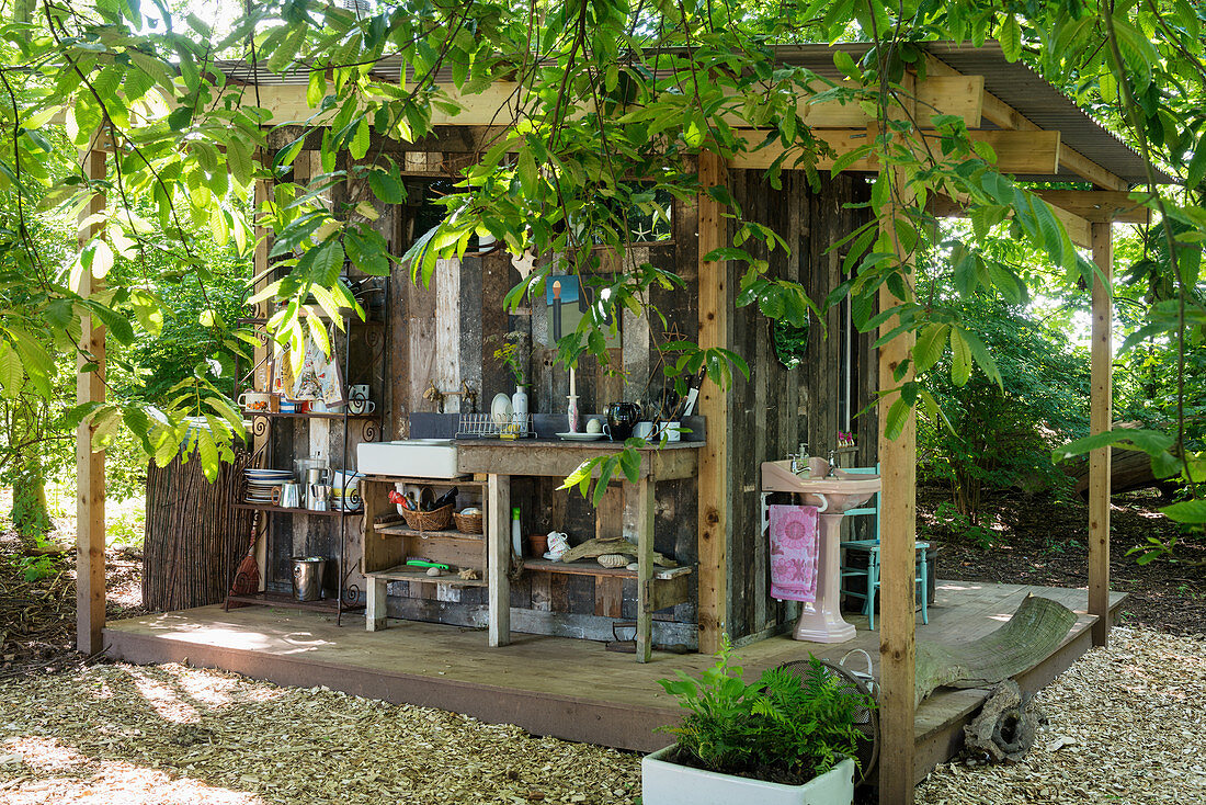 Outdoor kitchen and bathroom on façade of small wooden shed