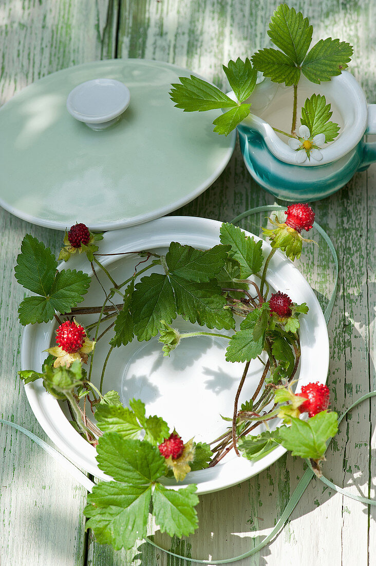 Tendrils of mock strawberries in soup tureen and wild strawberry flowers in milk jug decorating table