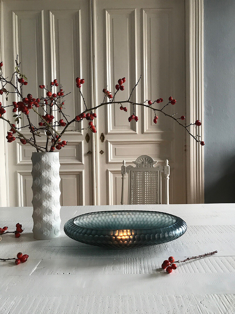 Glass bowl and branches of rose hips on table in front of antique wooden door
