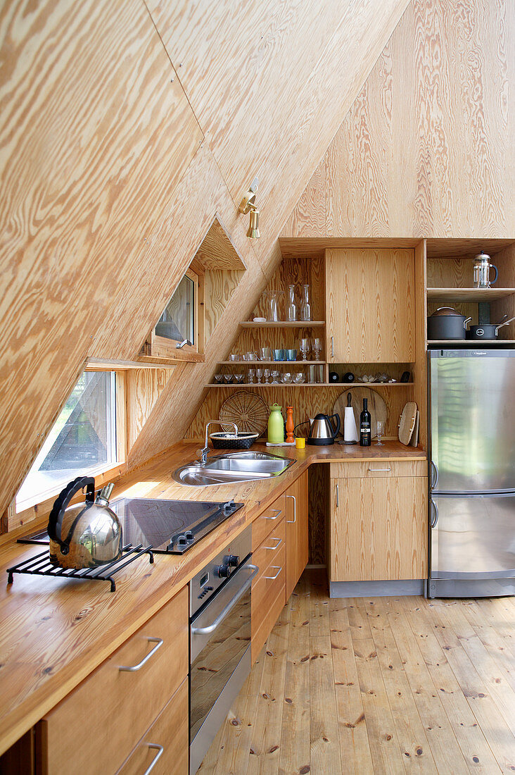 Fitted kitchen with sloping, wood-panelled wall