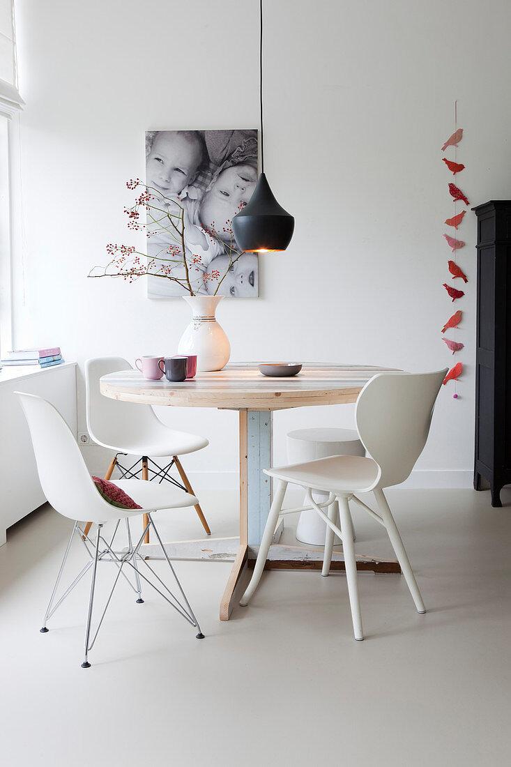 Verschiedene weiße Stühle am runden Tisch aus Altholz