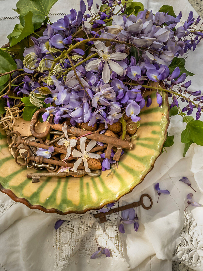 Clematis, wisteria, vintage keys and almonds in ceramic bowl