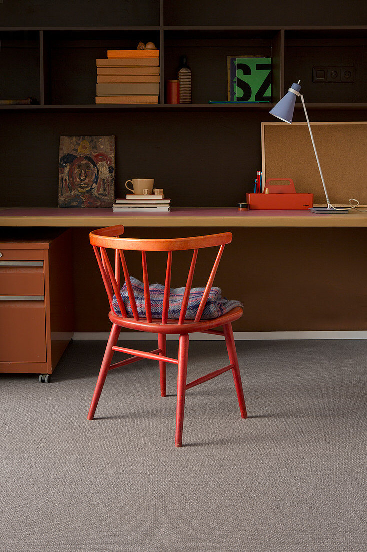Red spoke-back chair at desk in study in shades of red and orange