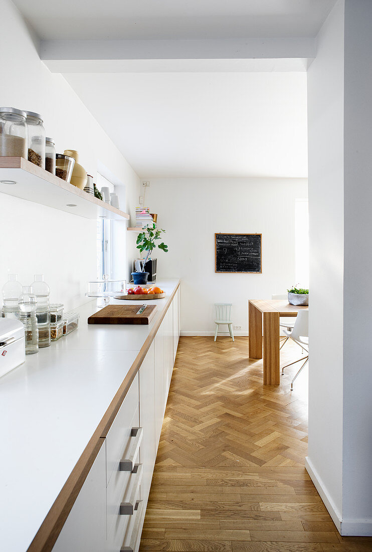 Long, continuous, white kitchen counter running from kitchen to dining room