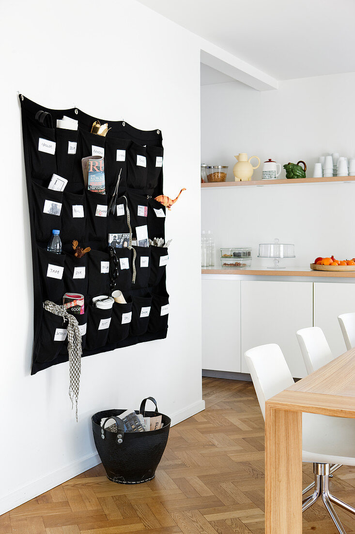 Fabric organiser on wall behind dining table in open-plan kitchen