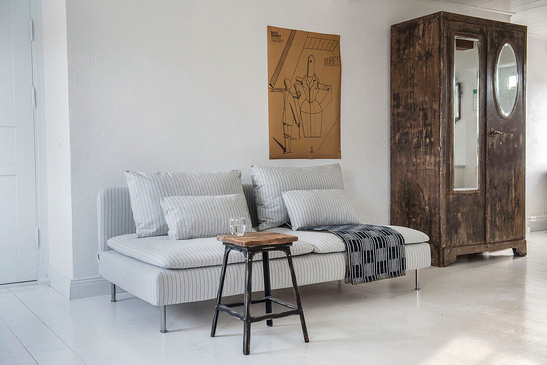 Stool used as coffee table in front of grey-striped sofa on white floor