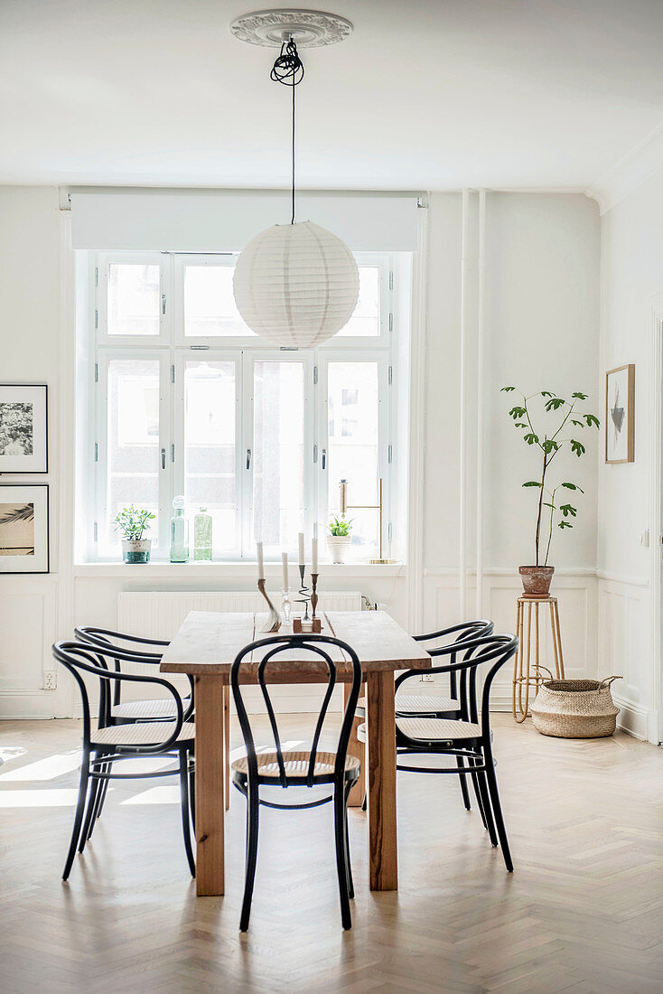 Black bistro chairs around dining table in period interior with panelled walls