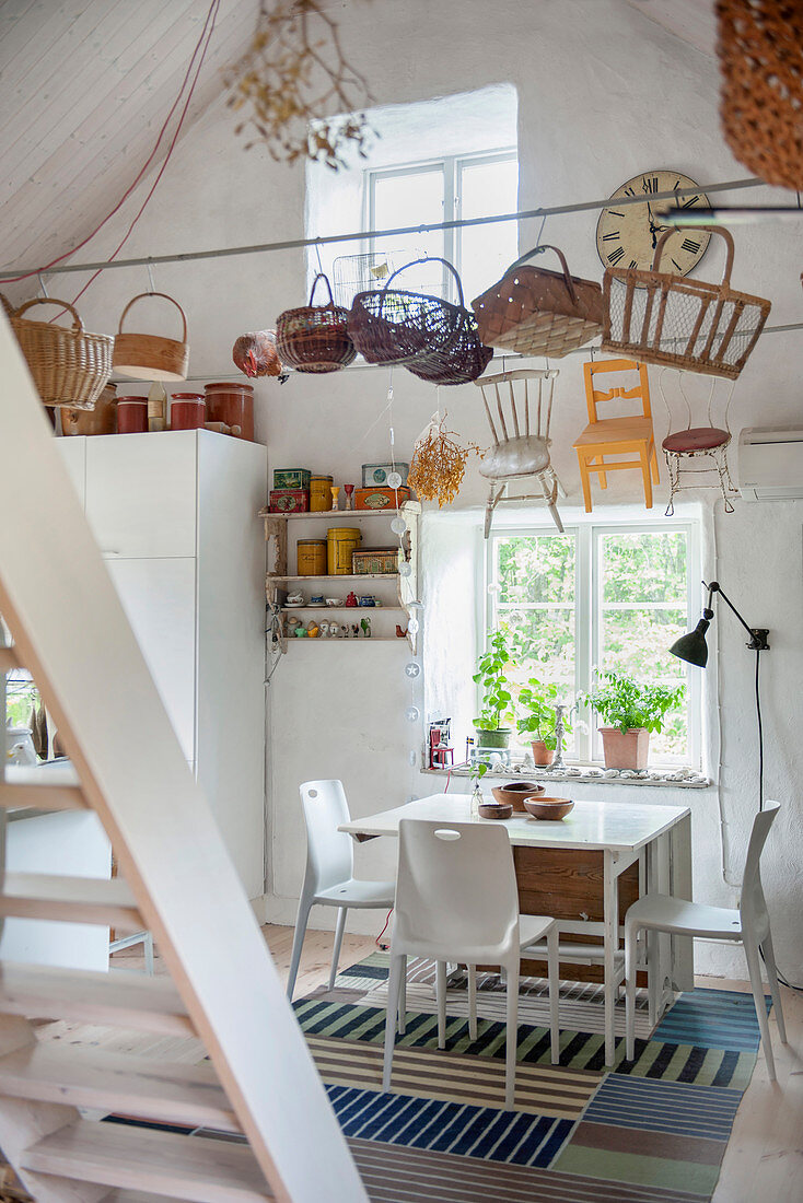 Baskets hanging above dining set in rustic white kitchen-dining room