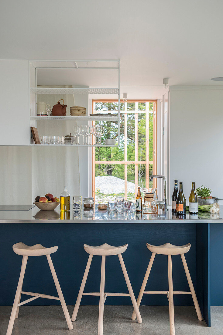 Three-legged barstools at blue kitchen counter in open-plan kitchen