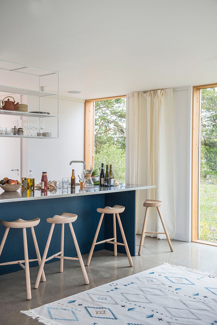 Three-legged barstools at blue kitchen counter in open-plan interior