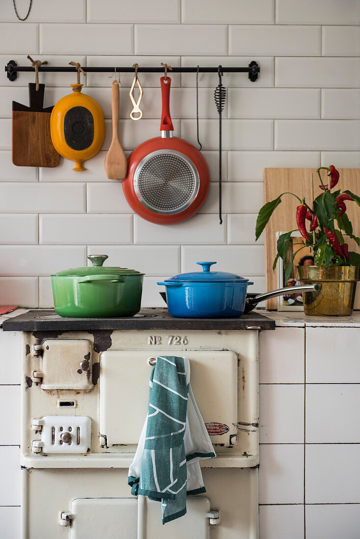 Colourful pans on old wood-burning stove below hook rail