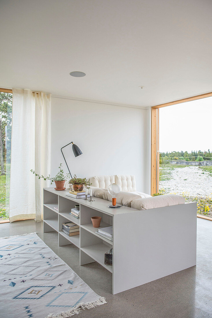Shelves used as partition behind sofa in front of panoramic window