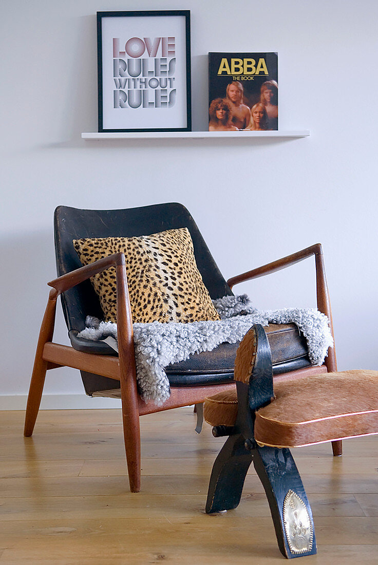 Leopard-print cushion on retro armchair with footstool