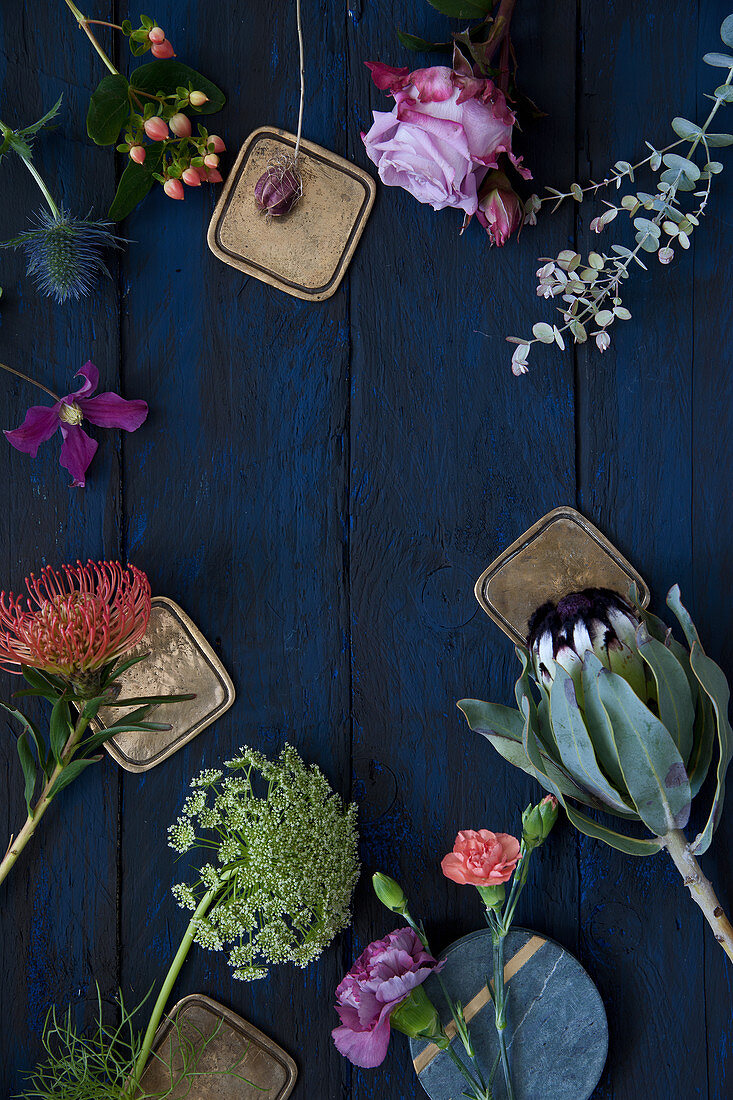 Roses, pinks, eucalyptus, clematis, proteas, Banksia, St. John's wort, sea holly and wild carrot on blue surface