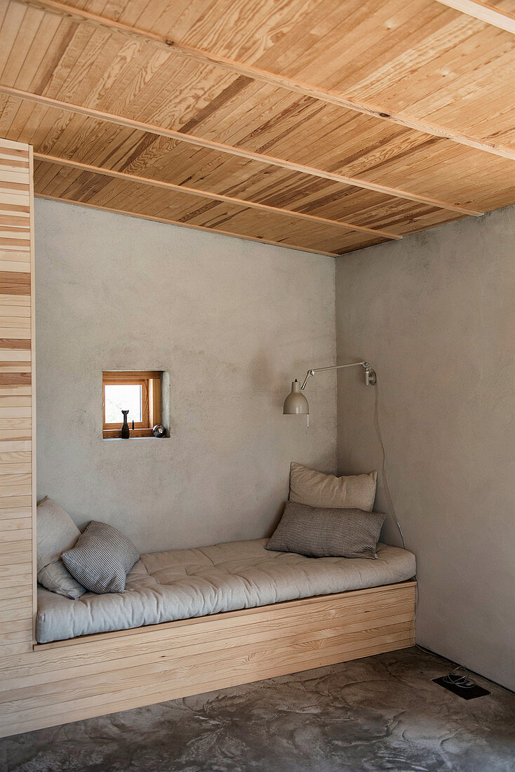 Seating area with bench fitted in niche, grey wall and wooden ceiling