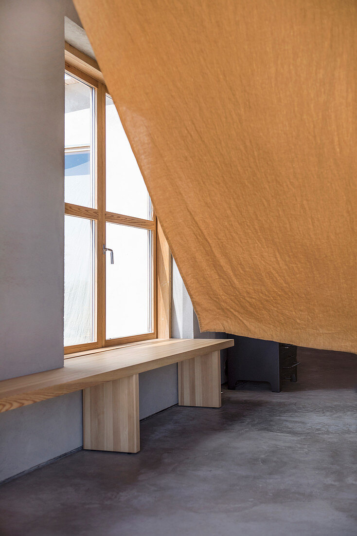 Wafting rough curtain in front of window seat
