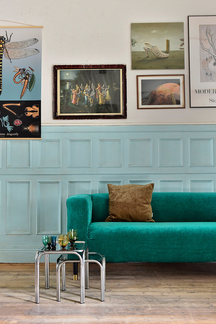 Emerald-green-sofa against pale blue panelled wainscoting below gallery of pictures
