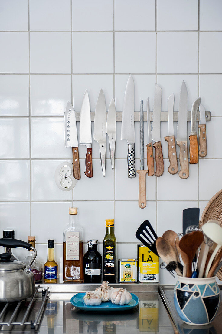 Magnetic knife rack on tiled wall in kitchen