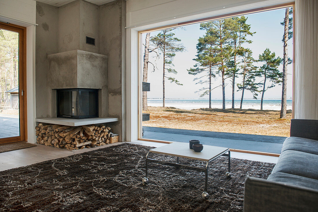 Square corner fireplace in living room with view of sea through panoramic window