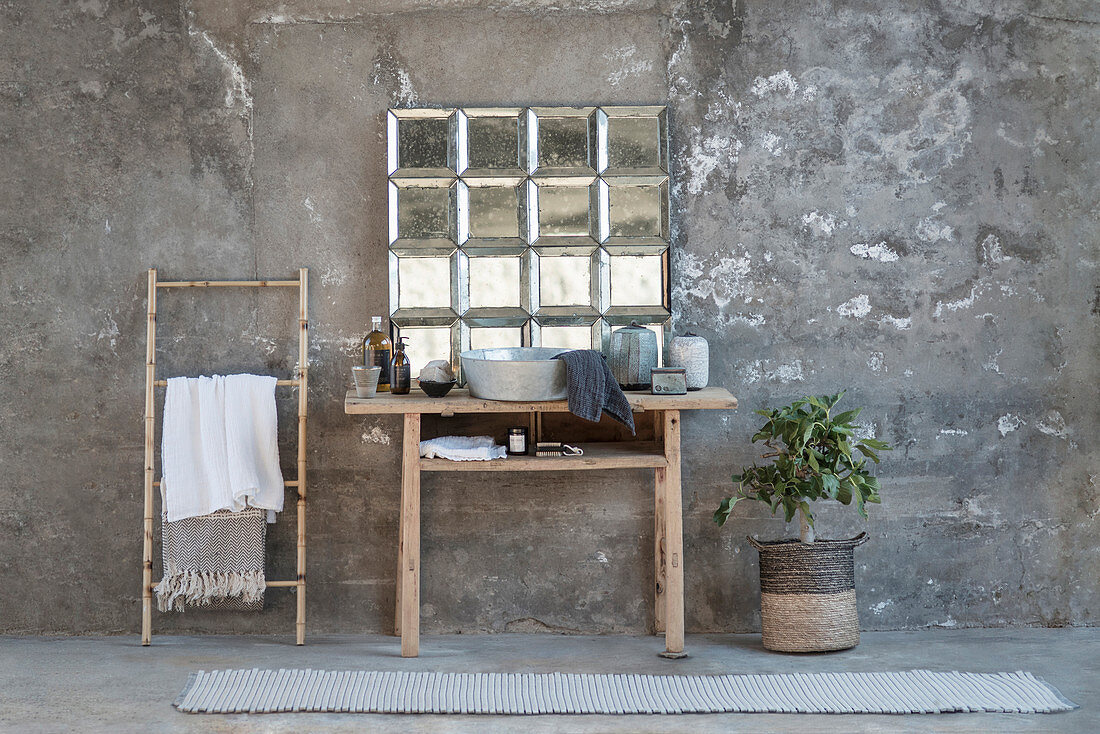 Towel rail next tosink on rustic wooden table below glass-brick window