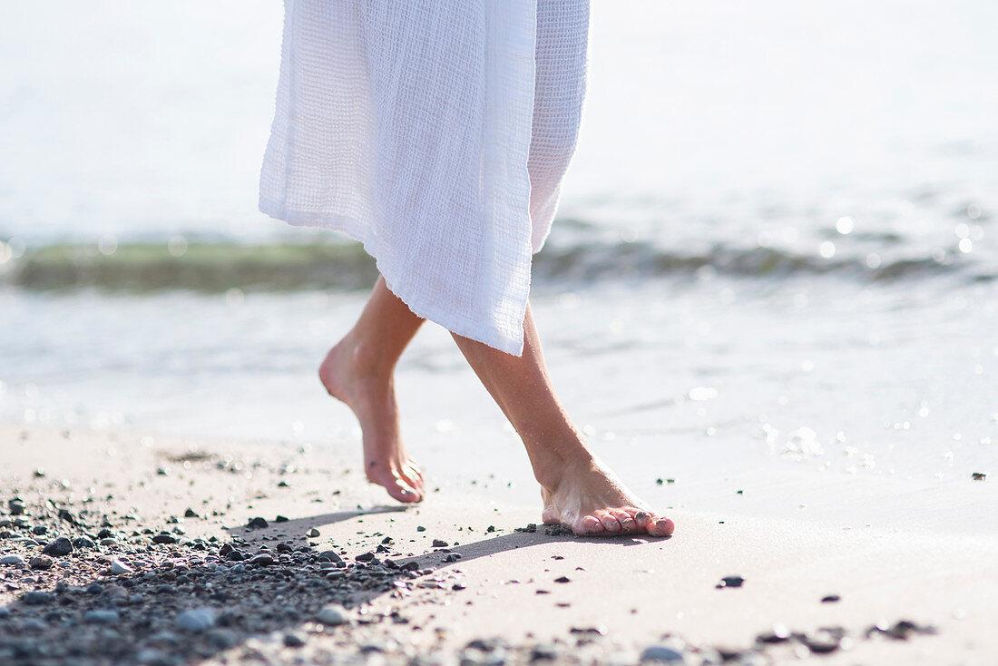 Woman wearing white bathrobe on beach