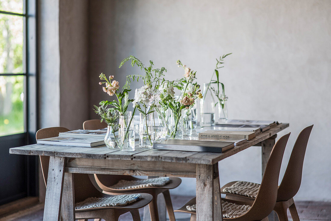 Flowers in various glass containers and books on rustic wooden table