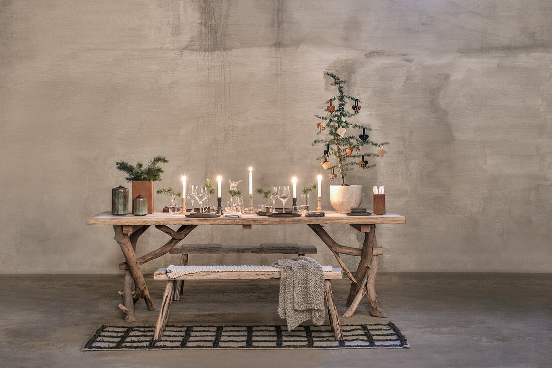 Festively decorated, rustic wooden table with frame made from branches