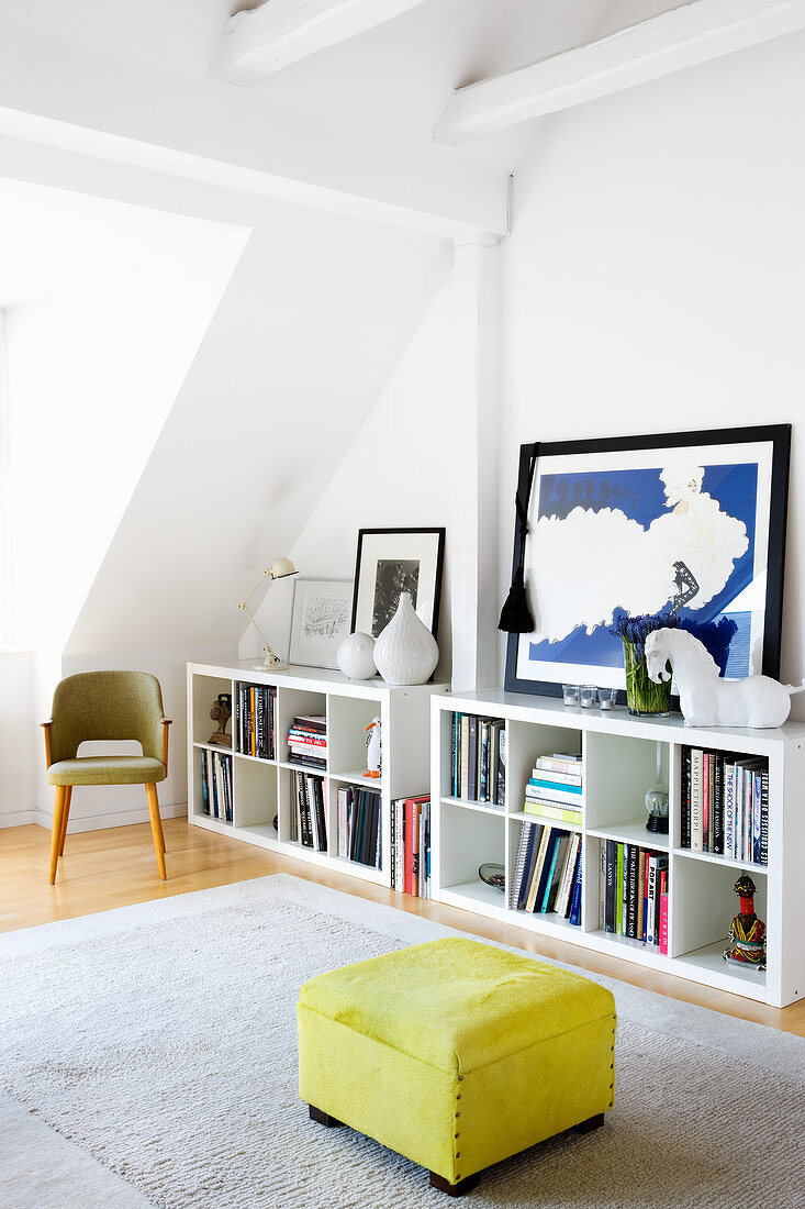 Yellow ottoman next to white shelves in living room
