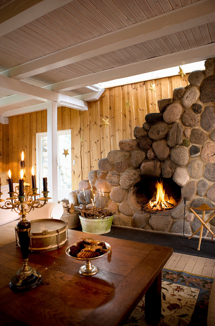 Open fireplace in wall clad in boulders in country-house-style living room