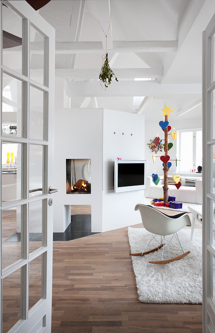 View into white living room with exposed ceiling structure and open fire