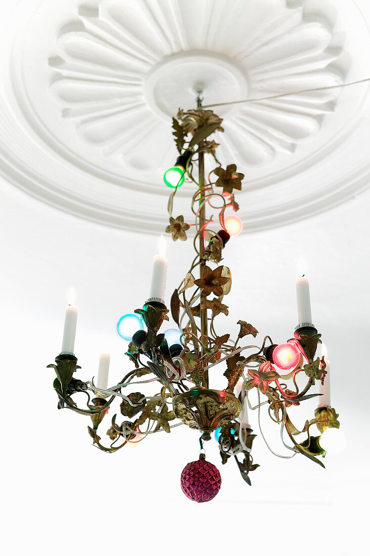 Colourful fairy lights wrapped around pretty chandelier hanging from ceiling rose