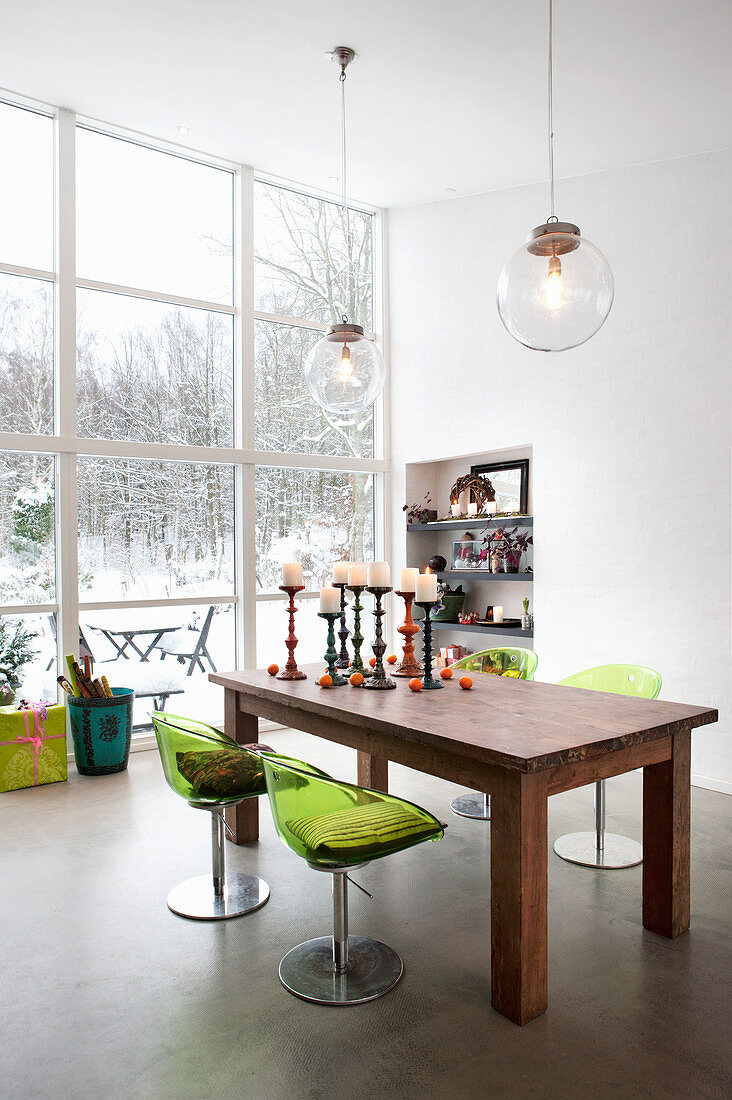 Green acrylic chairs around wooden table next to window with view of snowy garden
