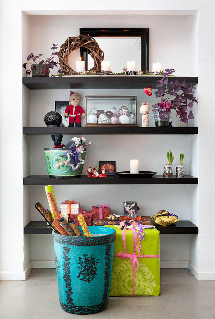 Basket of wrapping paper and wrapped gift in front of shelves in niche
