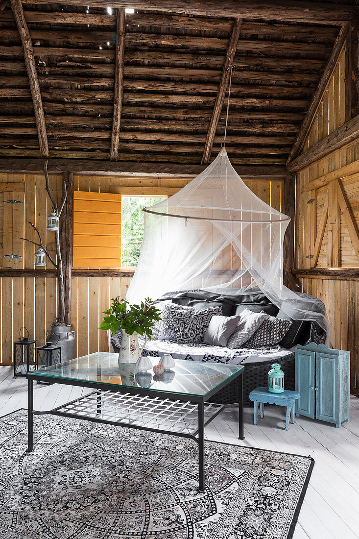 Canopy over sofa in living room in converted barn
