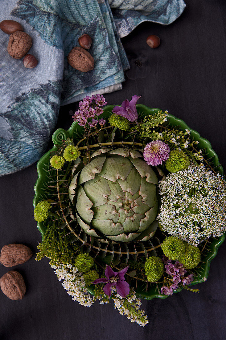 Artichokes, chrysanthemums, blue throatwort, waxflower, clematis and eucalyptus in bowl
