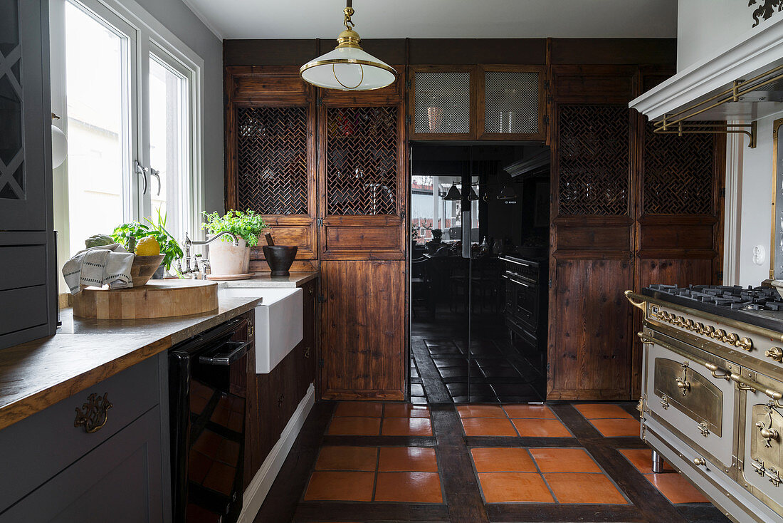Rustic country-house kitchen with dark wooden cabinets and pantry