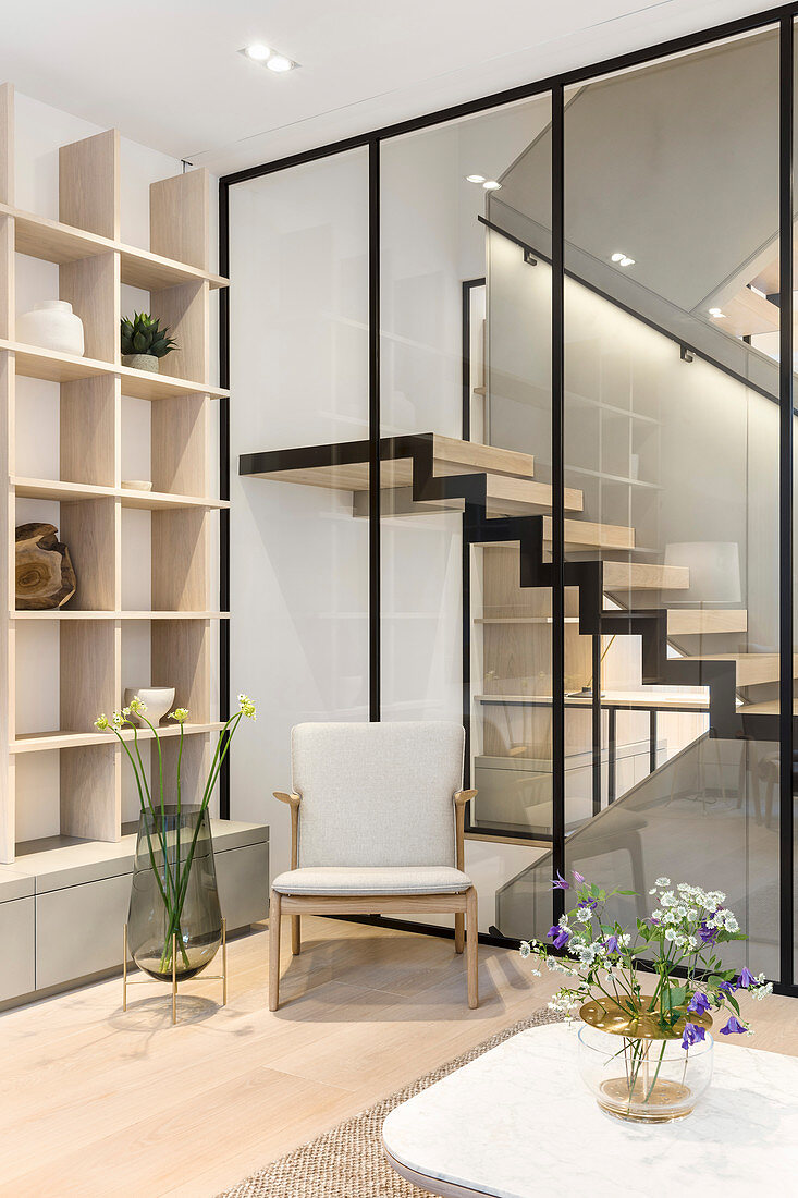 Armchair in living room with glass wall looking into stairwell