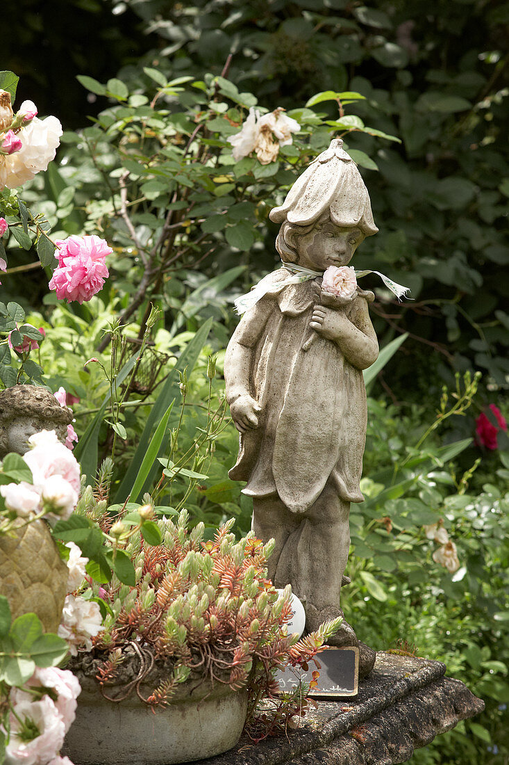 Flower fairy statue next to roses and Jenny's stonecrop planted in bowl