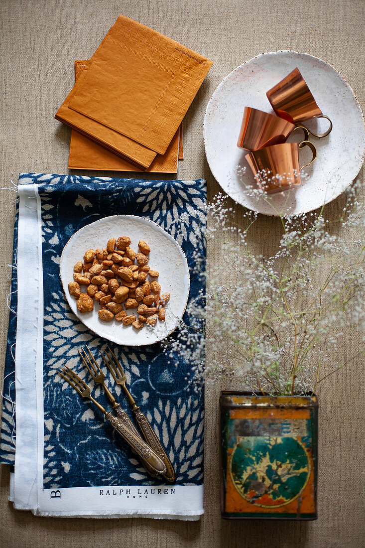 Flowering twigs in vintage tin, forks, peanuts, napkins and mocha coffee cups