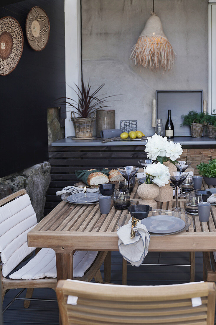 Set table in natural shades on terrace with exotic accessories