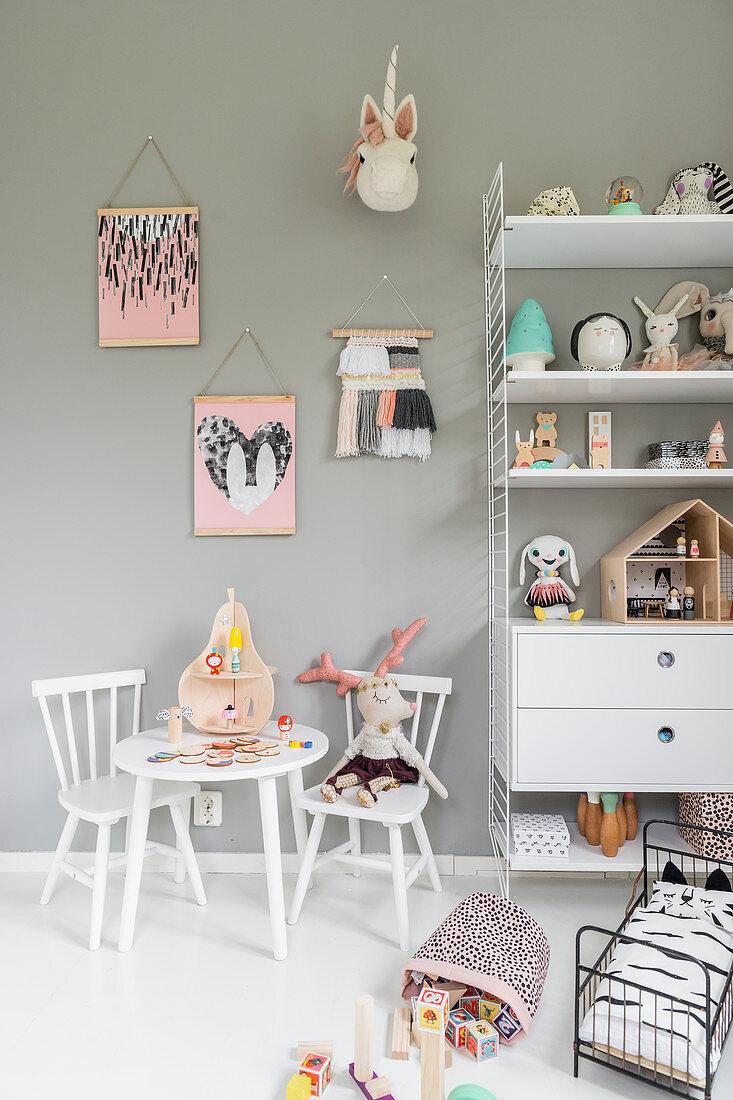 Kindertisch und Regal vor grauer Wand im Kinderzimmer