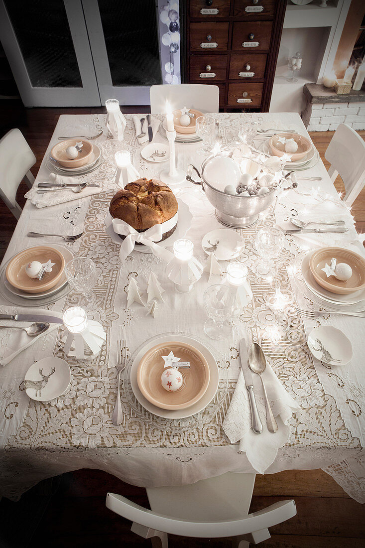 Top view of table festively set in white with lace tablecloth and tealight holders