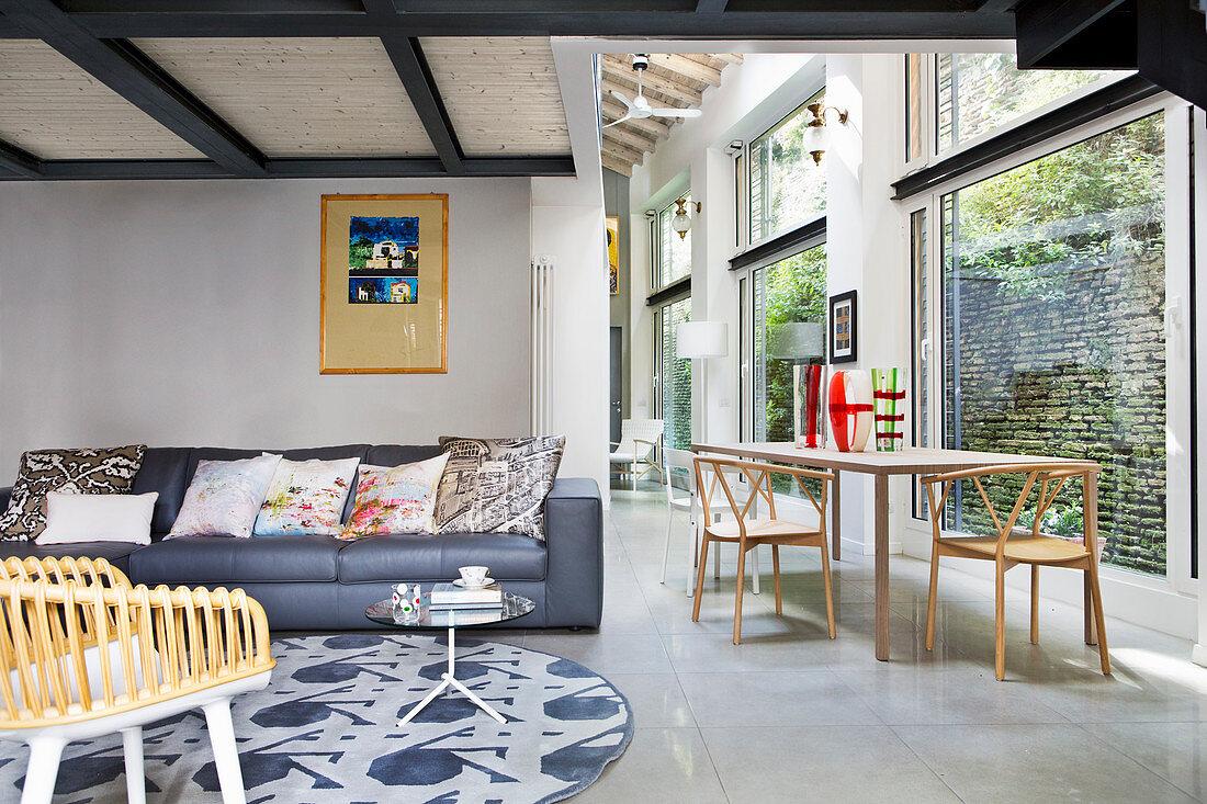 Loft-Wohnung mit Wohnbereich und Esstisch im Durchgangsbereich neben deckenhohen Fensterfronten