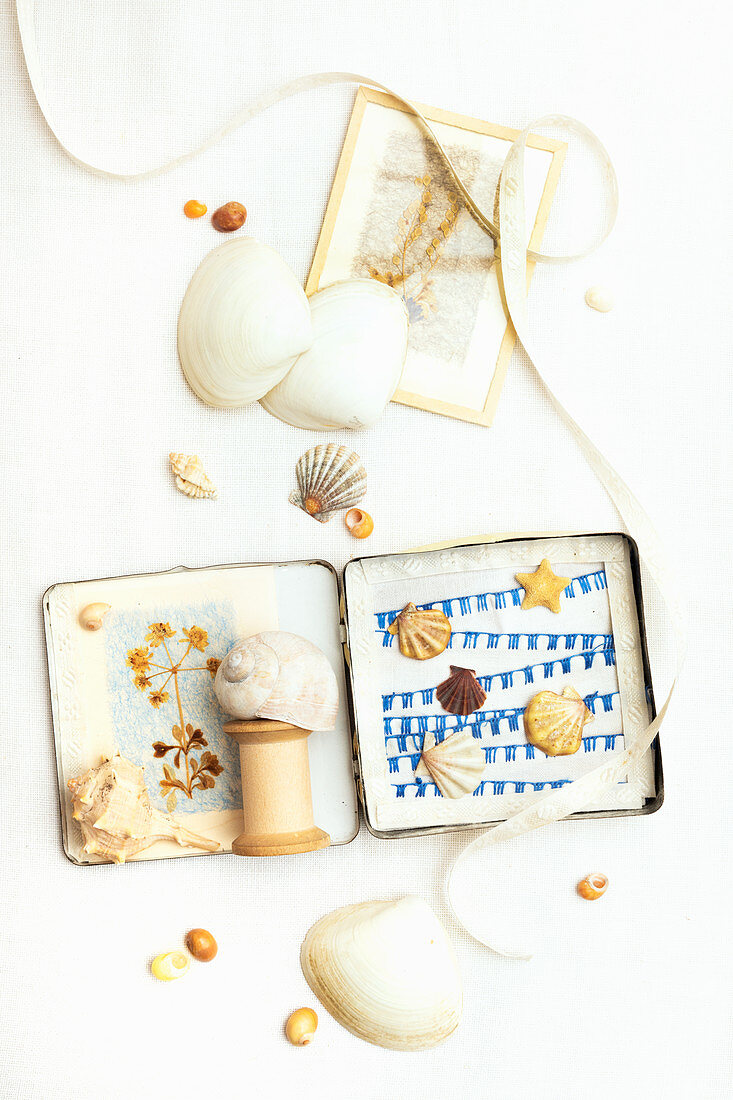 Old tin decorated with seashells, reel of thread, dried flowers and ribbons
