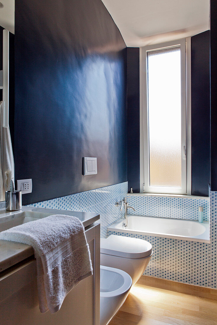 Miniature bathtub in small bathroom with black walls