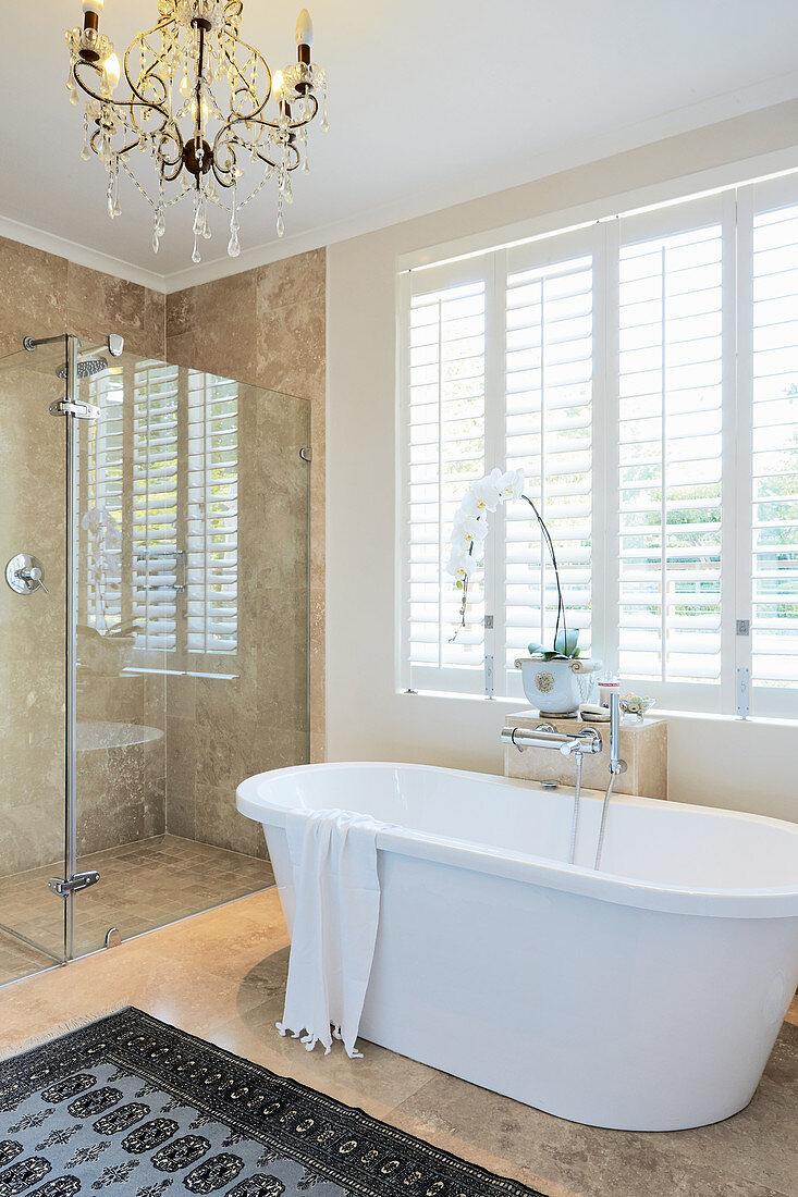 Free-standing bathtub and glazed shower area in elegant bathroom
