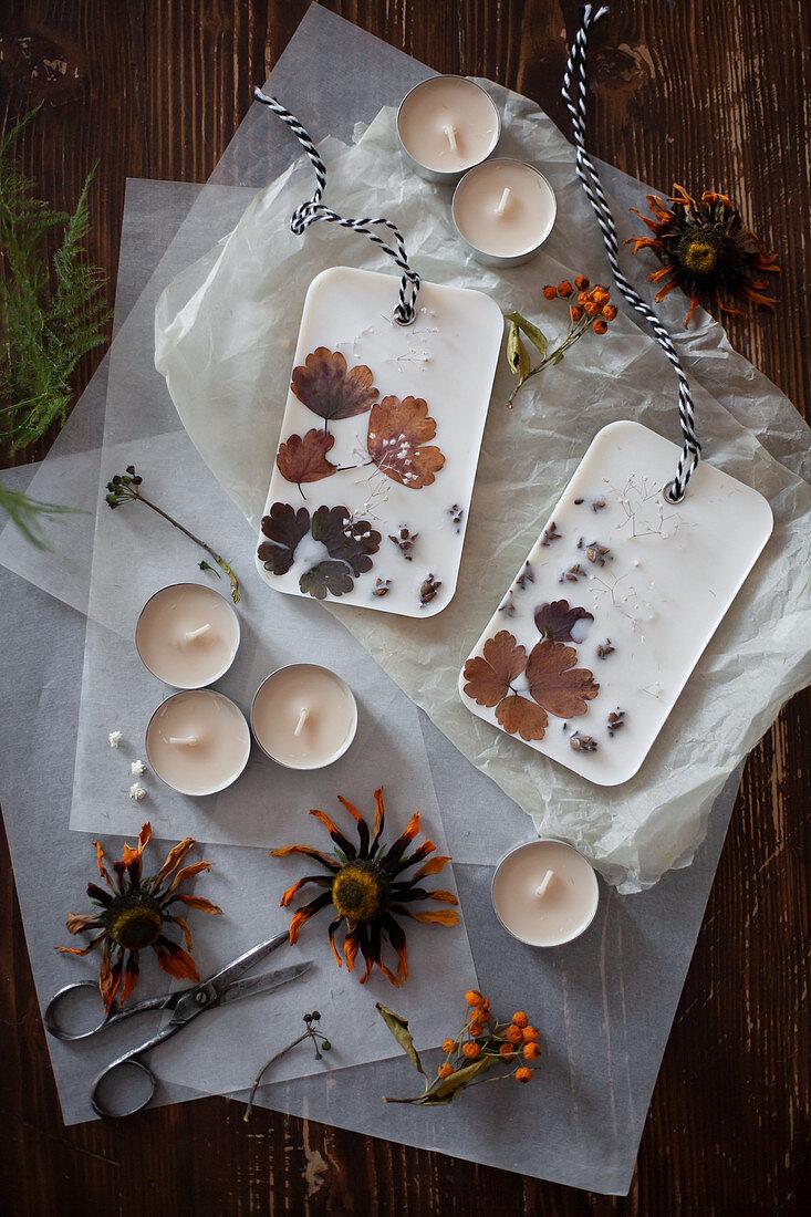 Selbstgemachtes Duftwachs mit Blüten und Blättern auf Seidenpapier